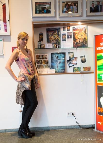 Julie Boehm in front of her exhibition promo: FARBWELTEN